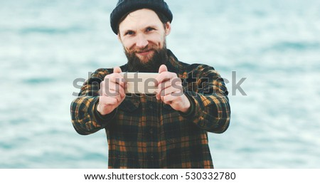Bearded Man taking selfie using Smartphone at sea Travel Fashion Lifestyle and modern technology concept happy emotions positive portrait