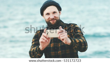 Bearded Man taking selfie using Smartphone at sea Travel Fashion Lifestyle and modern technology concept happy smiling emotions
