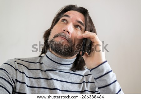 Bearded man talking on the phone in the living room