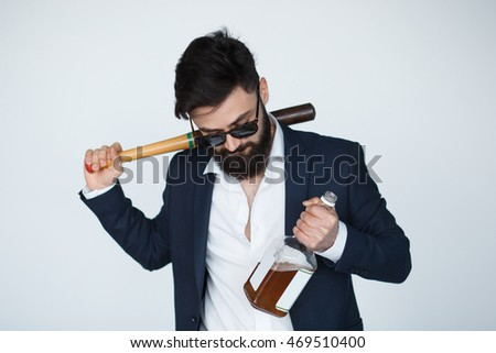 bearded man wearing black suit and sunglasses holding a bat and bottle of whiskey. Drunk mafia boss