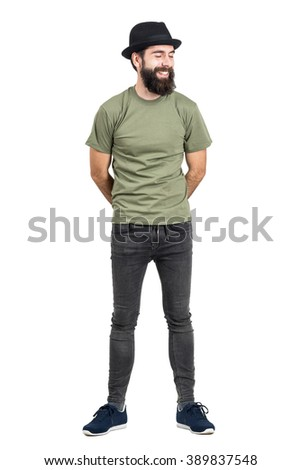Bearded man wearing hat and t-shirt laughing carefree with eyes closed. Full body length portrait isolated over white studio background. - stock photo