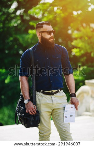 bearded man with a map in hand looking away