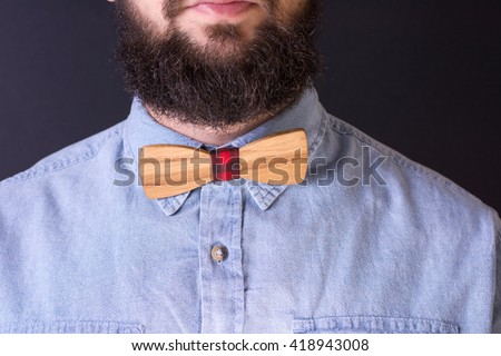 Bearded man with a wooden bow tie close up - stock photo