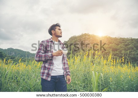 Bearded man with cup of morning coffee walking in the flower field.