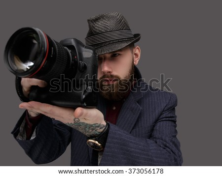 Bearded man with dslr camera. Isolated on grey background. - stock photo