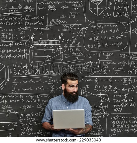 Bearded man with laptop. Chalkboard background with formulas. - stock photo