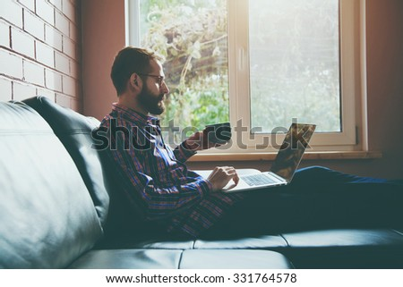 bearded man with laptop drinking coffee or tea - stock photo