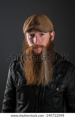 Bearded man with leather jacket and flat hat.