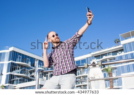 Bearded man with longboard make a selfie on phone