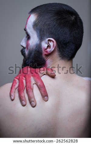 Bearded man with red painted hands embracing himself. Profile from the back, face painted in tribal makeup. Head and shoulders. - stock photo