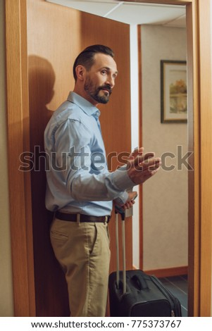 bearded man with suitcase looking away while entering hotel room