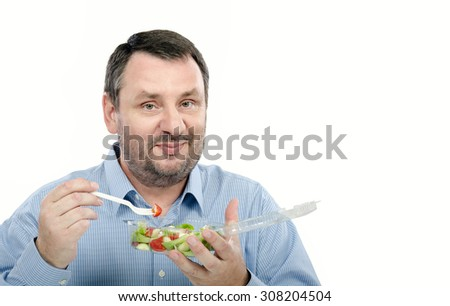 Bearded man with takeaway salad. Middle aged man is holding a plastic transparent container with vegetable salad by left hand. In right hand, he is clasping white fork with small cherry tomato. - stock photo