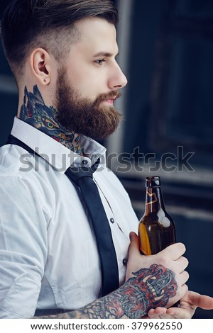 Bearded man with tattooes on his arm in a white shirt drinking beer. - stock photo