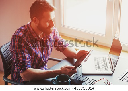 bearded man working with laptop and digital tablet in morning sunlight - stock photo