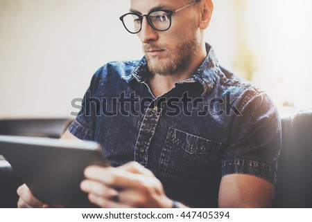 Bearded manager work tablet device modern Interior Design Loft Building.Man relax Vintage sofa use contemporary computer hand.Blurred background.Creative business startup Idea.Closeup,Film effect - stock photo