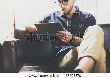 Bearded marketing specialist working digital tablet modern Interior Design Loft Office.Man relax classic sofa use contemporary device Hand.Blurred Background.Creative Process Business Startup Idea - stock photo