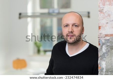 Bearded middle-aged balding man with a beard leaning on a grunge wall indoors looking at the camera, close up head and shoulders with copyspace - stock photo