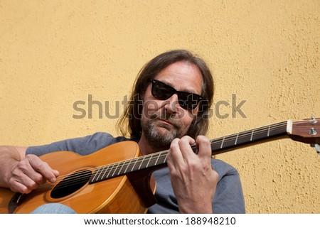 Bearded middle-aged man in sunglasses with his long hair in a ponytail sitting in the sunshine playing the guitar against a beige exterior building wall