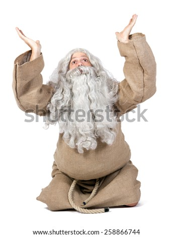 Bearded monk praying with hands up isolated on white background. Excitement believer asks the favor of God. The holy man invokes the heaven with his hands over his head. - stock photo