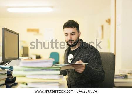Bearded office clerk working with files