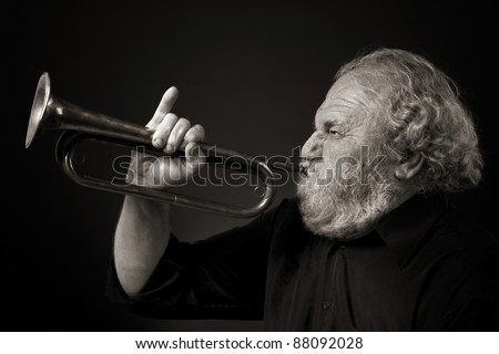 Bearded old man blowing a bugle with gusto - stock photo
