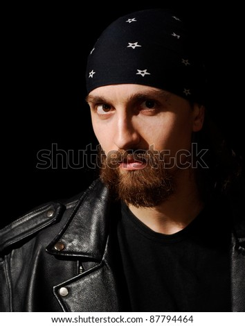 bearded rocker in leather jacket over black background