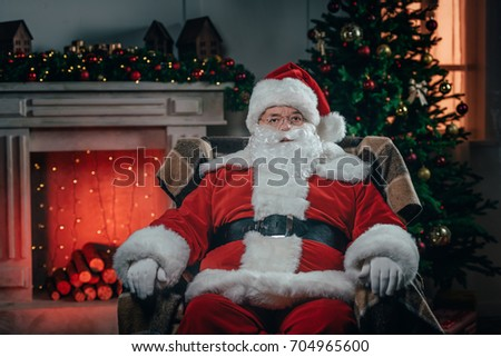 bearded santa claus in traditional red costume sitting in armchair near fireplace