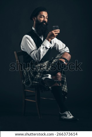Bearded Scotsman enjoying a nightcap sitting in a chair in his kilt in the darkness holding a glass of whiskey or brandy