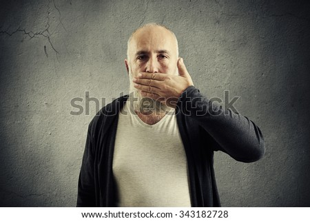 bearded senior man covering his mouth and looking at camera over grey wall - stock photo