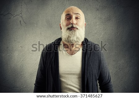 bearded senior man doing air kiss over dark background
