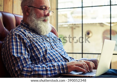 bearded senior man in glasses sitting on the couch and working with laptop at home - stock photo