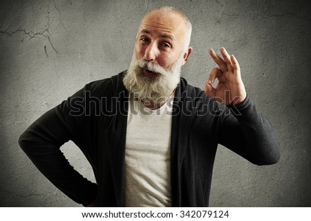 bearded senior man showing ok sign and looking at camera over grey wall - stock photo