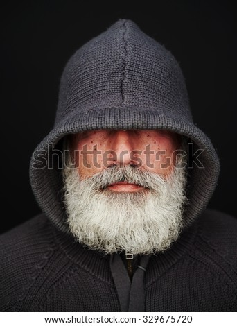 bearded senior man under the hood over black background