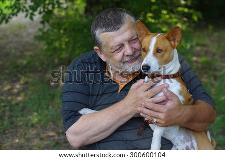 Bearded senior man with his cute dog (basenji) - stock photo