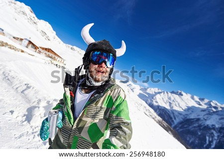 Bearded skier in a green outfit with horns with a can in his hands on top of snow-capped mountains against the blue sky