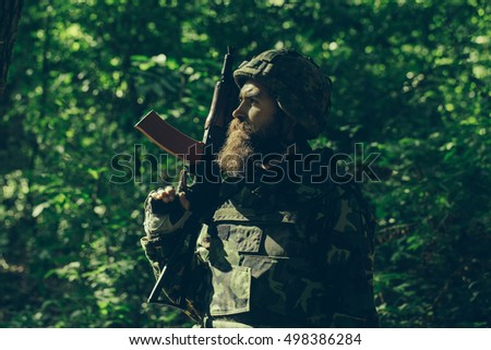 Bearded soldier in camouflage and with the gun in the forest