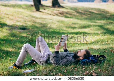 Bearded student man hipster reading a book and relax in park. EXAM. College. Education - stock photo