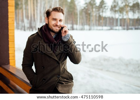 bearded, stylish and handsome man sits on the street in the winter