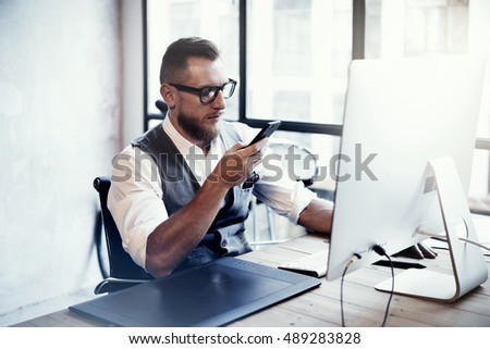 Bearded Stylish Young Man Wearing Glasses White Shirt Waistcoat Working Modern Loft Startup Process.Creative Person Using Smartphone Texting Message.Drawing Tablet Desktop Computer Wood Table.Blurred