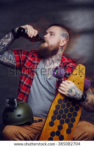 Bearded tattooed man drinking beer and holding longboard. - stock photo