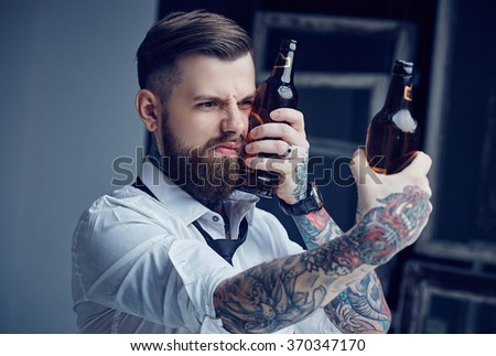 Bearded tattooed man holding beer bottles.