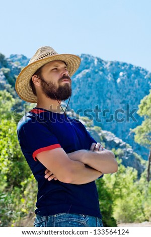 bearded traveler in a hat on a background of mountains