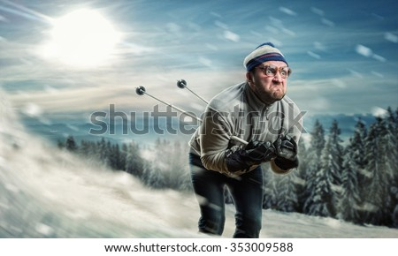 Bearded vintage skier in glasses skiing fast while snowing
