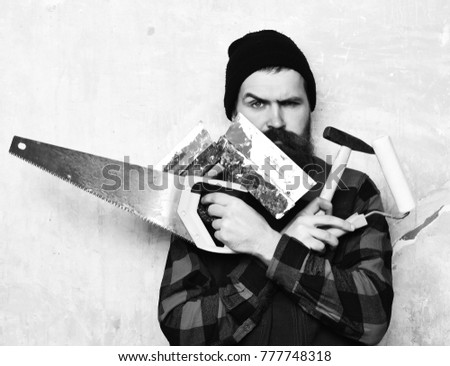 bearded worker, long beard, brutal caucasian hipster with moustache holding various building tools: saw, hammer, roller paint with serious face on studio wall background
