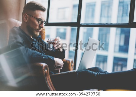 Bearded young businessman working on modern loft office. Man sitting in vintage chair, holding glass water. Using contemporary notebook, panoramic windows background. Horizontal, film effect.  - stock photo