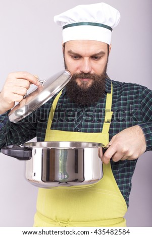 Bearded young chef  looking into the pot over gray background - stock photo