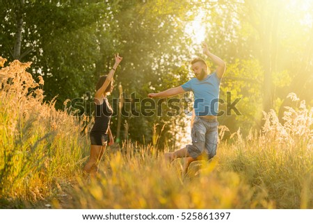 Bearded young man jumps up next to a woman  in the summer forest at sunny day