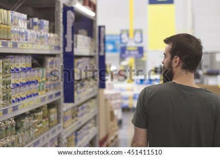 Bearded young man walks through a supermarket aisle while looking products.