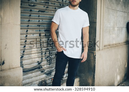 Bearded young man wearing white blank t-shirt and blue jeans, standing on the street - stock photo