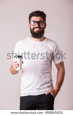 Bearded young man with coffee cup and smiling while standing against grey background - stock photo
